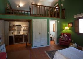 Salón de color verde con altillo