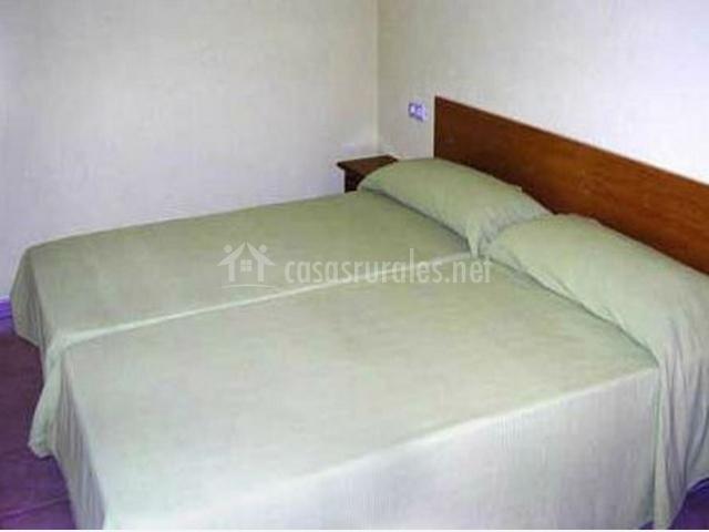2 camas juntas con ropa de cama blanca en casa rural