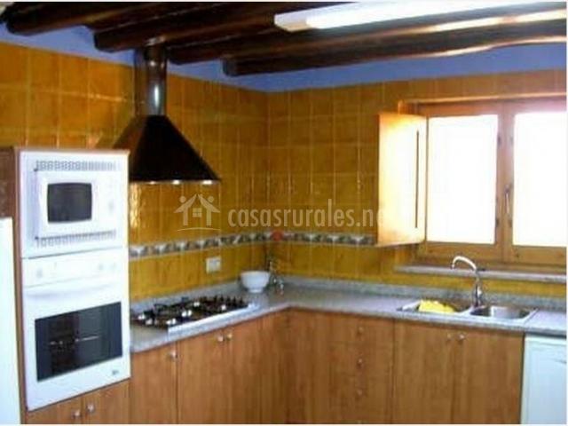 Cocina con baldosa ocre en la pared y ventana de casa rural.