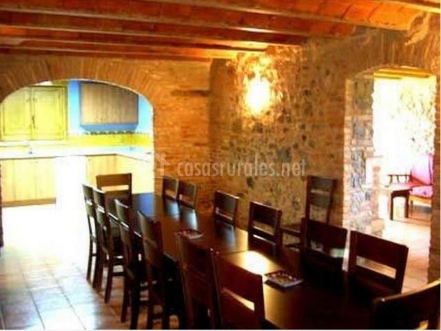 Comedor con 2 mesas y sillas separado por pórtico de casa rural.