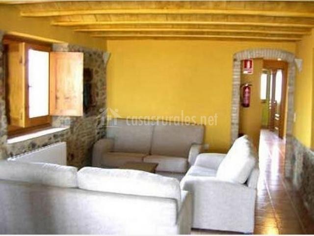 Salón con sofás blancos y radiador de casa rural.