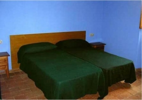 Habitación de 2 camas con colchas verdes y pared azul