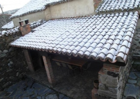 Tejado nevado de la zona de barbacoa en el exterior de la casa rural