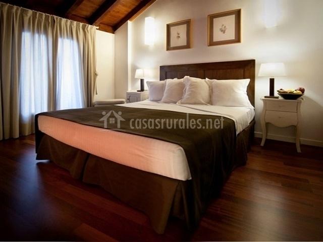 Habitación con cama de matrimonio y techo con vigas
