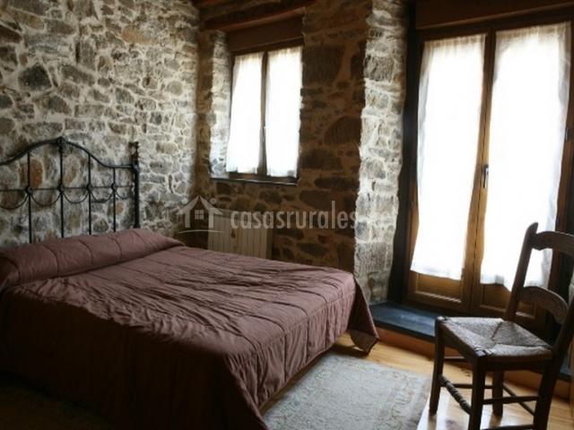 Dormitorio con cama doble y grandes ventanas