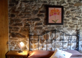 Double bed in bedroom with stone walls
