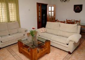 Sala de estar con mesa de comedor y televisor en la esquina