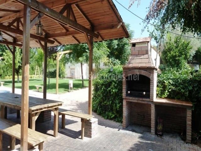 Barbacoa de obra y gran porche de madera cubierto