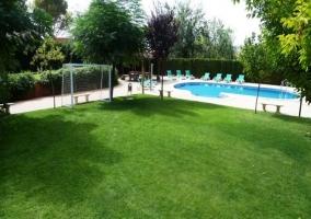 Jardín con piscina hamacas y portería