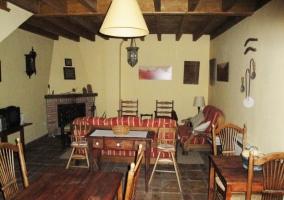Zona de comedor en el interior del salón de la casa rural con varias mesas