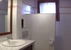 Aseo con ducha y pila redonda sobre la que se encuentra el espejo