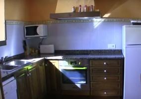Cocina con armarios de madera y detalles anaranjados