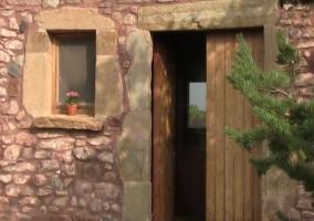 Vistas de la entrada a la vivienda con puerta de madera