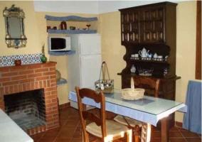 Chimenea en la cocina con mesa y electrodomésticos