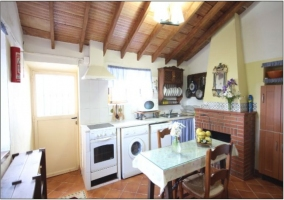 Cocina con techo abohardillado. Chimenea, mesa y electrodomésticos