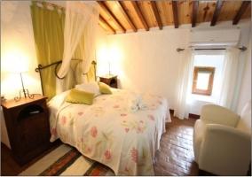 Dormitorio con cama de matrimonio. Techo con vigas de madera, mesita de noche y sofá