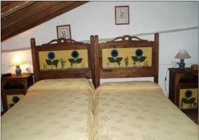 Dormitorio con dos camas individuales. Cabeceros y mesilla de noche con flores