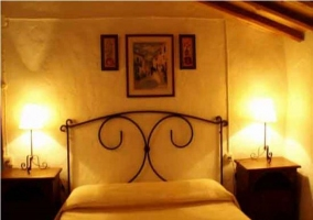Dormitorio de matrimonio con cabecero de hierro. Luces encendidas, adornos y mesillas