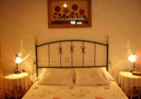 Dormitorio de matrimonio con colchas de flores. Cabecero de hierro, mesillas y luces encendidas
