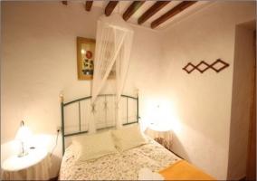 Dormitorio doble. Edredones estampados, mesita de noche y techo con vigas de madera