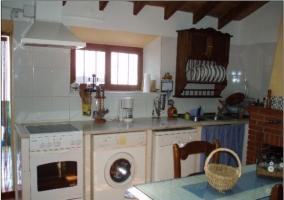 Electrodomésticos en la cocina con vigas de madera. Horno, lavavajillas, y lavadora