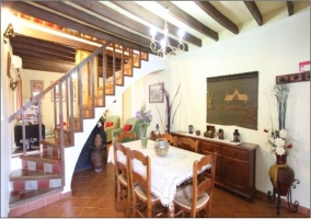 Escaleras, mesa del comedor y adornos. Techo con vigas de madera