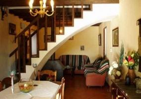 Salón-comedor con mesa, sillones, decoración y escaleras en forma de arco