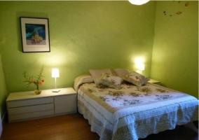 Habitación con cama matrimonial con mesita amplia y paredes verdes