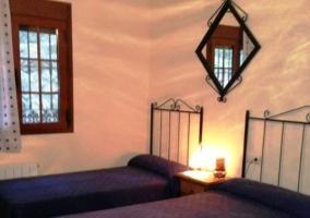 Dos camas individuales con lamparita encendida