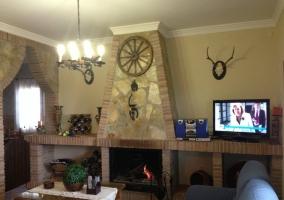 Salón con televisión plasma y chimenea de piedra