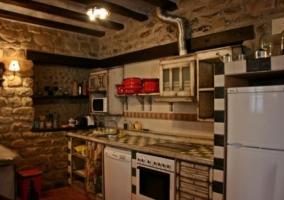 Cocina completa con paredes de piedra y horno