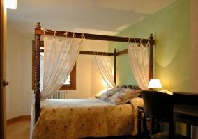 Dormitorio de matrimonio con dosel antiguo de madera