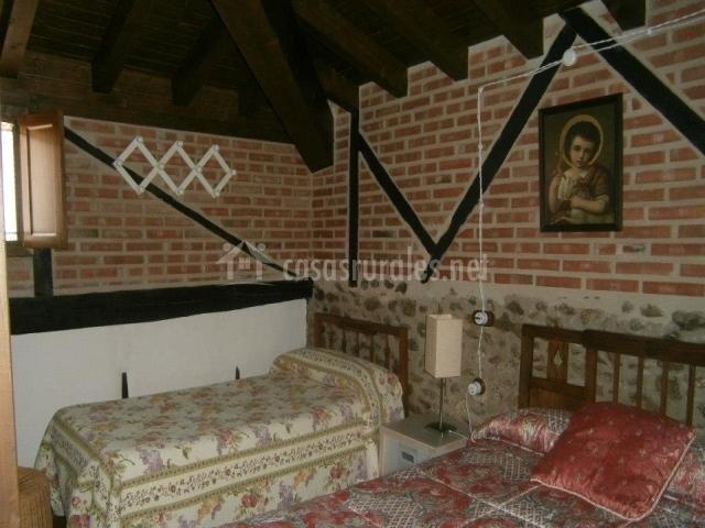 Dormitorio con camas individuales y pared de ladrillo
