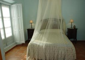 Dormitorio con cama de matrimonio con mosquitera