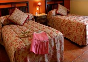 Dormitorio con dos camas con cojines encima