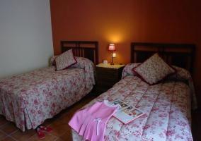 Dormitorio con pared naranja y dos camas
