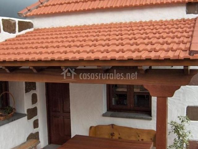 Vistas de la fachada de la casa con mesa de madera