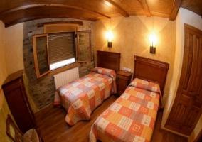 Dormitorio con dos camas separadas y baño