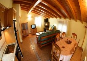 Salón-comedor y cocina con mesa, sofá, chimenea y televisión