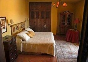 Dormitorio doble con colcha blanca y cabecero original