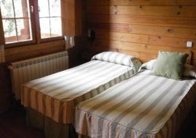 Dormitorio con un par de camas y cojines