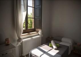 Dormitorio con cama junto a la ventana