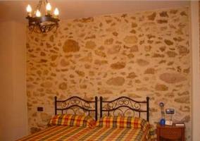 Dormitorio doble con camas juntas y pared empedrada
