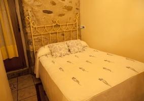 Cama de matrimonio en dormitorio con pared de piedra y lisa