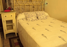 Dormitorio con cama doble y mesilla blanca