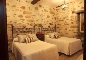 Dormitorio con dos camas individuales y pared con piedras