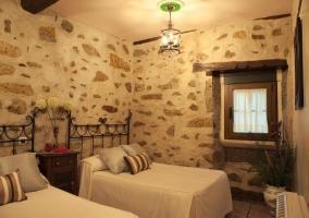 Dormitorio con paredes de piedras y dos camas individuales