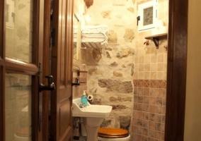 Entrada al aseo con lavabo e inodoro y pared de piedra