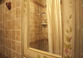 Espejo del aseo con la ducha reflejada