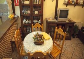 Mesa redonda del comedor con sillas y televisor al lado